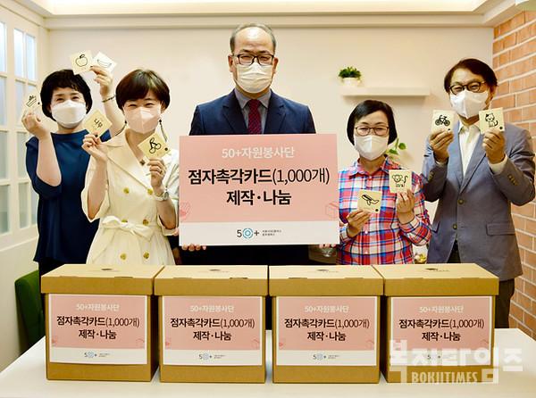 서울시50플러스재단이 자원봉사자들과 함께 점자촉각카드 전달 기념촬영을 하고 있다.